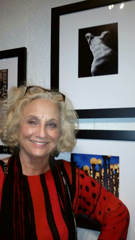 Photographer Susan Schelling stands in front of her photographs. Photo credit: Demi Goddess Chronicle
