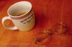 Marcia Nasatirs' reading glasses and coffee. Photo credit Demi Goddess Chronicle