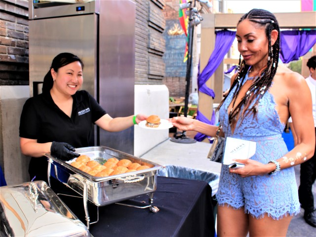 A Block Party guest receives a Morton's Steakhouse slider from its event manager Courtney Nakagawa. Photo credit: DemiGoddessChronicle.com